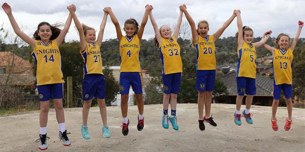 Girls Under 11.3 Knights team jump to celebrate their finals performance.
